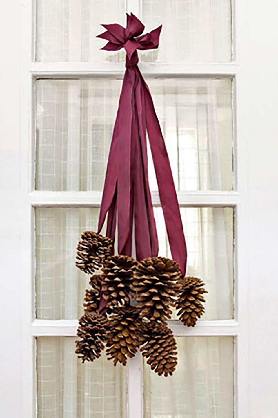 """<p>Not all DIY front-door decor requires a foam wreath form. To make this elegant cluster, we selected 8 four- to six-inch pinecones and 8 two-foot-long pieces of silk ribbon. Use a hot-glue gun to adhere the last two inches of each ribbon to the base of a cone. After the glue dries, collect all the ribbon ends and stagger them so that the cones fall at varying lengths. Tie the ribbon ends together in a knot, trim the tips so they are uniform, and slip the knot over a finishing nail. </p><p><a class=""""link rapid-noclick-resp"""" href=""""https://www.amazon.com/Bulk-Package-Natural-Pinecones-24-Pack/dp/B077PNQTY3/ref=sr_1_3?tag=syn-yahoo-20&ascsubtag=%5Bartid%7C10050.g.1371%5Bsrc%7Cyahoo-us"""" rel=""""nofollow noopener"""" target=""""_blank"""" data-ylk=""""slk:SHOP PINE CONES"""">SHOP PINE CONES</a></p>"""