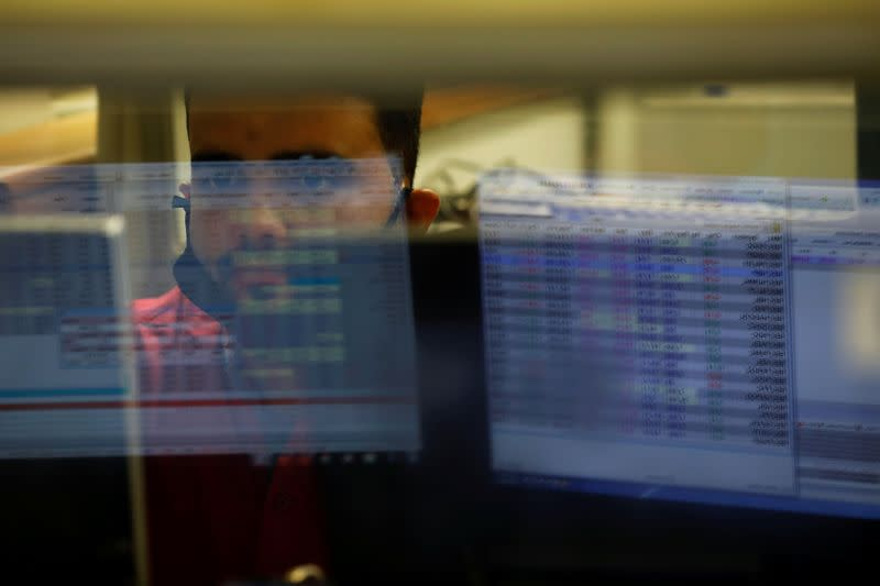 A computer screen is reflected in the glass window of a booth where a broker is monitoring the market in the halls of the Pakistan Stock Exchange, in Karachi