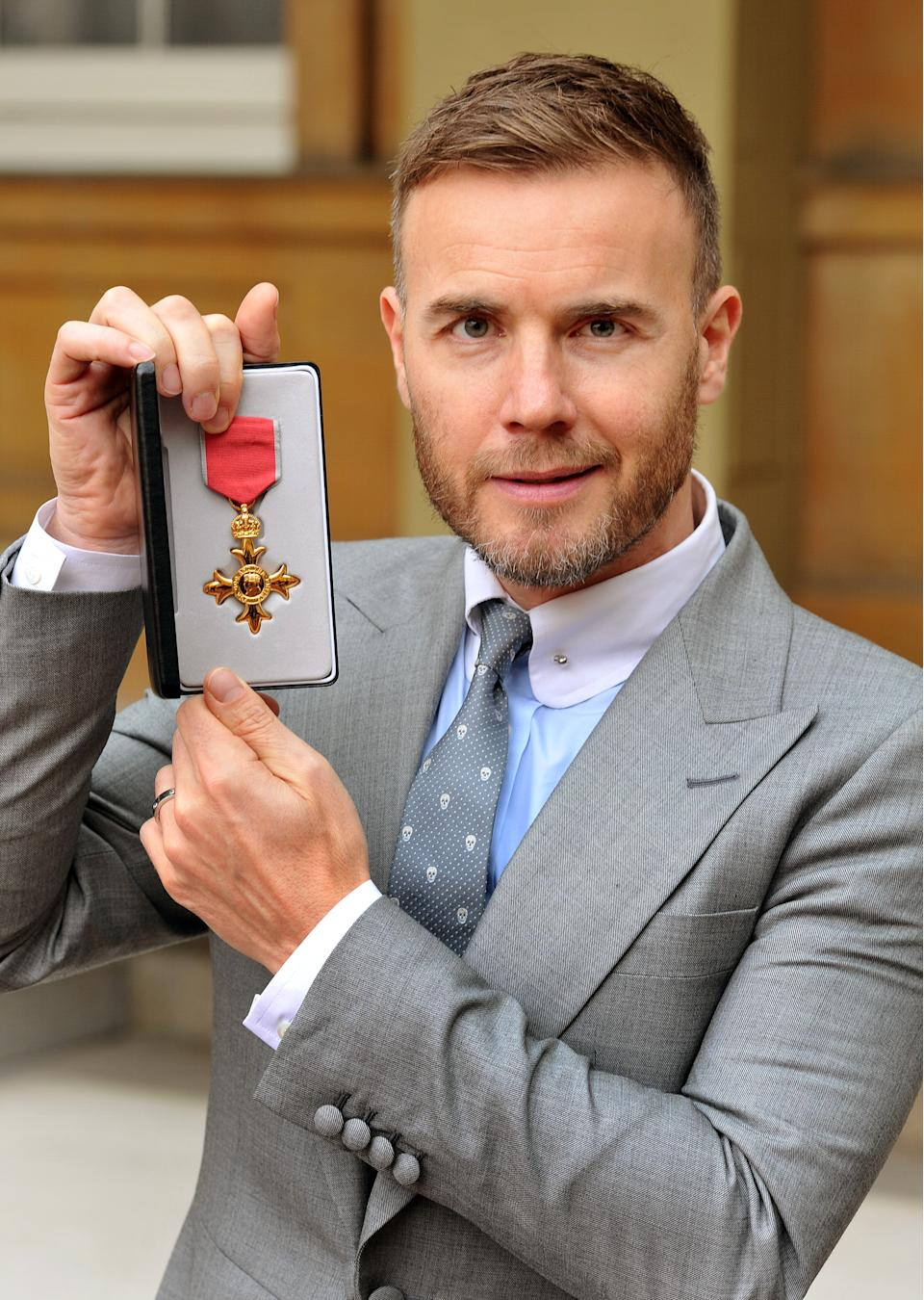 Gary Barlow holds his OBE, for services to the entertainment industry and to charity, which was awarded to him by Queen Elizabeth II during an Investiture ceremony at Buckingham Palace on November 21, 2012 in London, England. (Photo by John Stillwell/WPA Pool/Getty Images)