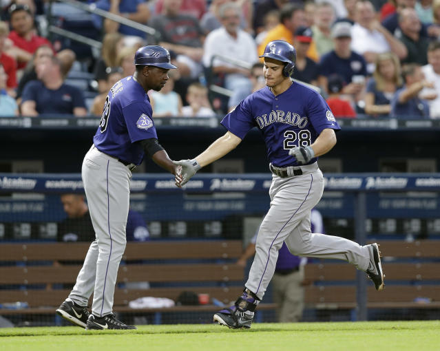 Colorado Rockies third baseman Nolan Arenado (28) is greeted by third base coach Stu Cole (39) as he rounds third base after hitting a home run in the fourth inning of a baseball game against the Atlanta Braves in Atlanta, Monday, July 29, 2013. (AP Photo/John Bazemore)