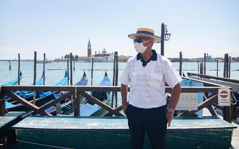 A gondolier waits for customers in Venice - Getty