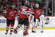 New Jersey Devils goaltender Keith Kinkaid, right, takes the ice while switching out with goaltender Cory Schneider, center, during the first period of an NHL hockey game, Friday, Dec. 14, 2018, in Newark. Schneider gave up three goals in the first period before being pulled. (AP Photo/Julio Cortez)