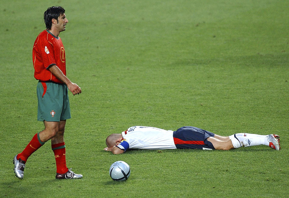 FILE - In this June 24, 2004 file photo Portugal's Luis Figo, left, stands over England's David Beckham during the Euro 2004 quarter final soccer match between England and Portugal at the Luz Stadium in Lisbon, Portugal. (AP Photo/Armando Franca, File)