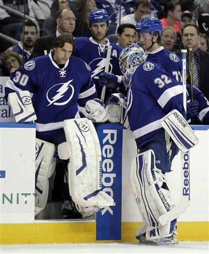 Tampa Bay Lightning goalie Dwayne Roloson (30) replaces goalie Mathieu Garon (32) after Garon was injured during the first period of an NHL hockey game against the Ottawa Senators on Tuesday, March 6, 2012, in Tampa, Fla. (AP Photo/Chris O'Meara)
