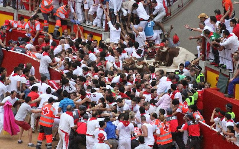 Runners trip and fall ahead of the bulls blocking the entrance to the bullring during the running of the bulls of the San Fermin festival, in Pamplona, Spain, Saturday, July 13, 2013. A total of 21 persons have been injured, two by gorings, as thousands of daredevils raced through the crowded streets of Pamplona in a hair-raising running of the bulls that ended in a crush on Saturday.(AP Photo/Joseba Etxeberria)