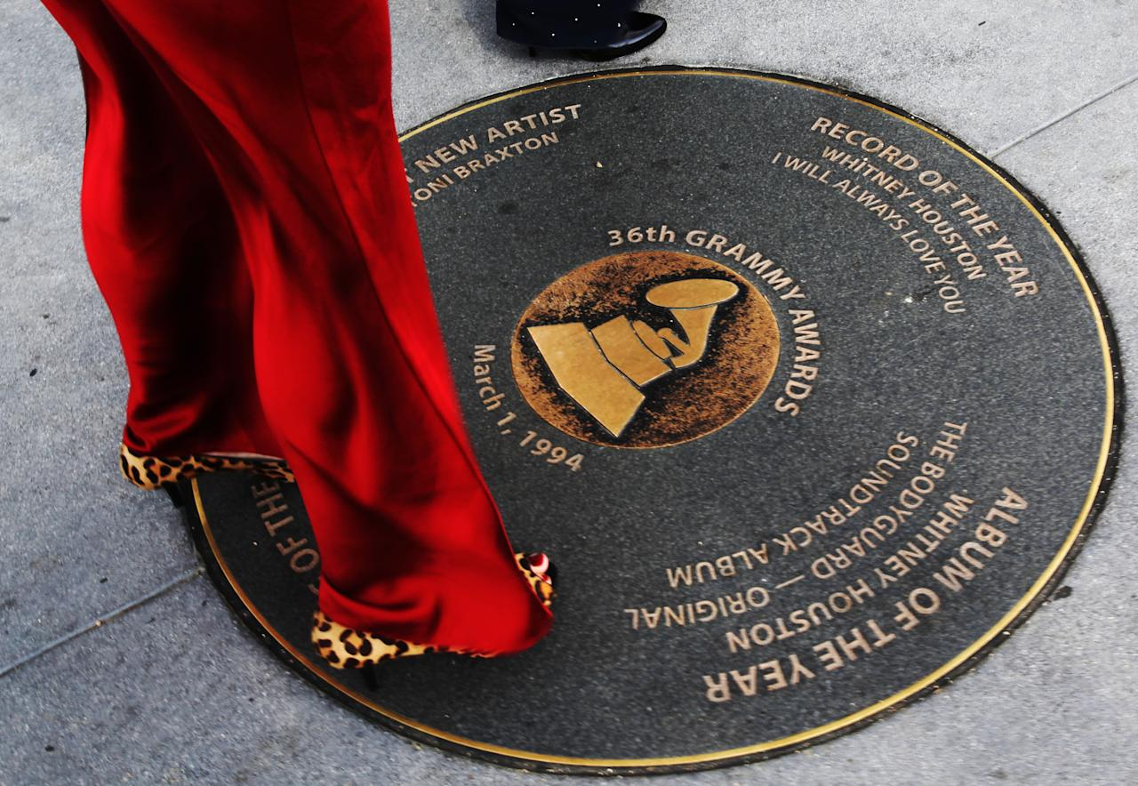 A woman arriving for tonight's Grammy awards looks at a Grammy sidewalk plaque, honoring Whitney Houston's wins for Record of the Year and Album of the Year in 36th Grammy Awards, outside the Grammy Museum in Los Angeles, Feb. 12, 2012. Houston died Saturday, Feb. 11, 2012, on the eve of the 54th Grammys, at the Beverly Hilton Hotel, where she was preparing to attend a pre-Grammy party. She was 48. (AP Photo/Reed Saxon)