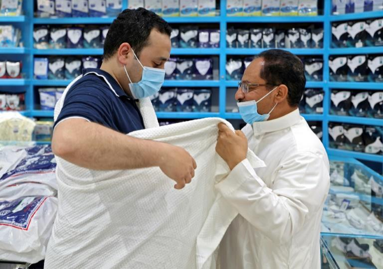 """Egyptian Mohammed El Eter who won the hajj """"lottery"""" tries the ceremonial ihram seamless white garment that symbolises unity among worshippers which he will wear for the annual pilgrimage"""