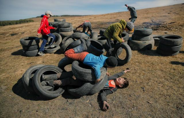 In this photo taken on Sunday, March 10, 2019, children play with used tires before a ritual marking the upcoming Clean Monday, the beginning of the Great Lent, 40 days ahead of Orthodox Easter, on the hills surrounding the village of Poplaca, in central Romania's Transylvania region. Romanian villagers burn piles of used tires then spin them in the Transylvanian hills in a ritual they believe will ward off evil spirits as they begin a period of 40 days of abstention, when Orthodox Christians cut out meat, fish, eggs, and dairy. (AP Photo/Vadim Ghirda)