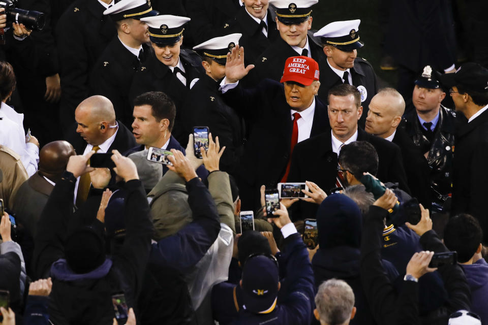 President Donald Trump waves after crossing the field at the end of the first half of an NCAA college football game between Army and Navy, Saturday, Dec. 14, 2019, in Philadelphia. (AP Photo/Matt Rourke)