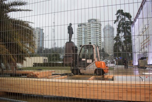 """In this photo taken on Thursday, Jan. 23, 2014 a statue of Lenin stands in a central park in Sochi, Russia, surrounded by temporary fencing where workers are putting up one of the Olympic """"live sites"""". The Russian Black Sea resort of Sochi is hosting the Winter Games on Feb. 7-23. (AP Photo/Nataliya Vasilyeva)"""