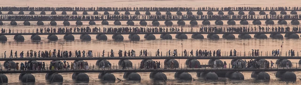 ALLAHABAD, INDIA - FEBRUARY 09: Hindu pilgrims make their way over pontoon bridges near Sangam, the confluence of the holy rivers Ganges, Yamuna and the mythical Saraswati, during the Maha Kumbh Mela on February 9, 2013 in Allahabad, India. The Maha Kumbh Mela, believed to be the largest religious gathering on earth is held every 12 years on the banks of Sangam, the confluence of the holy rivers Ganga, Yamuna and the mythical Saraswati. The Kumbh Mela alternates between the cities of Nasik, Allahabad, Ujjain and Haridwar every three years. The Maha Kumbh Mela celebrated at the holy site of Sangam in Allahabad, is the largest and holiest, celebrated over 55 days, it is expected to attract over 100 million people. (Photo by Daniel Berehulak/Getty Images)