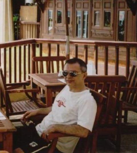 A man with sunglasses sits on outdoor furniture.
