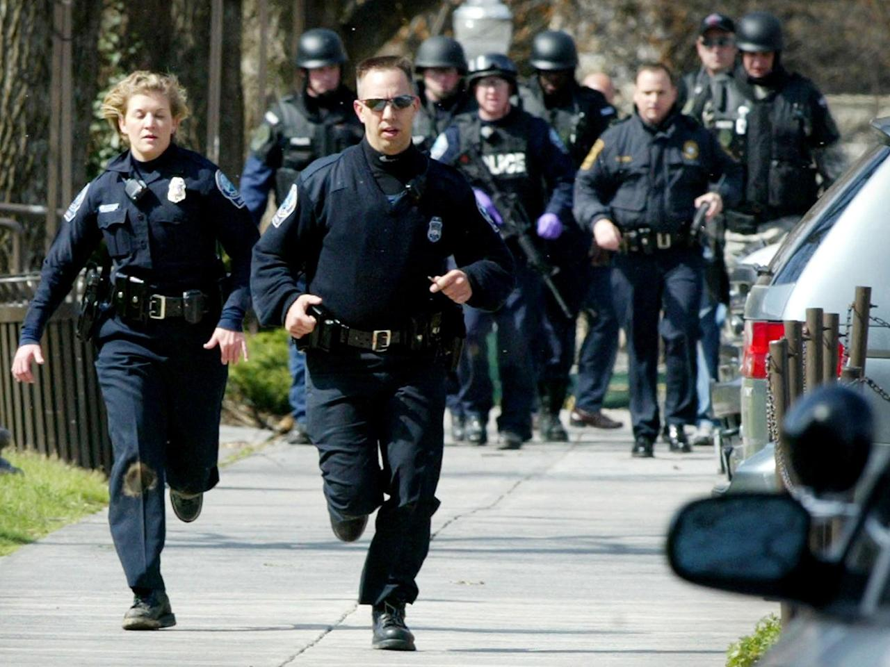 <p>Blacksburg police officers run from Norris Hall on the Virginia Tech campus in Blacksburg, Va., Monday, April 16, 2007. A gunman opened fire in a Virginia Tech dorm and then, two hours later, in a classroom across campus, killing 32 people. (Photo: Matt Gentry/The Roanoke Times/AP) </p>