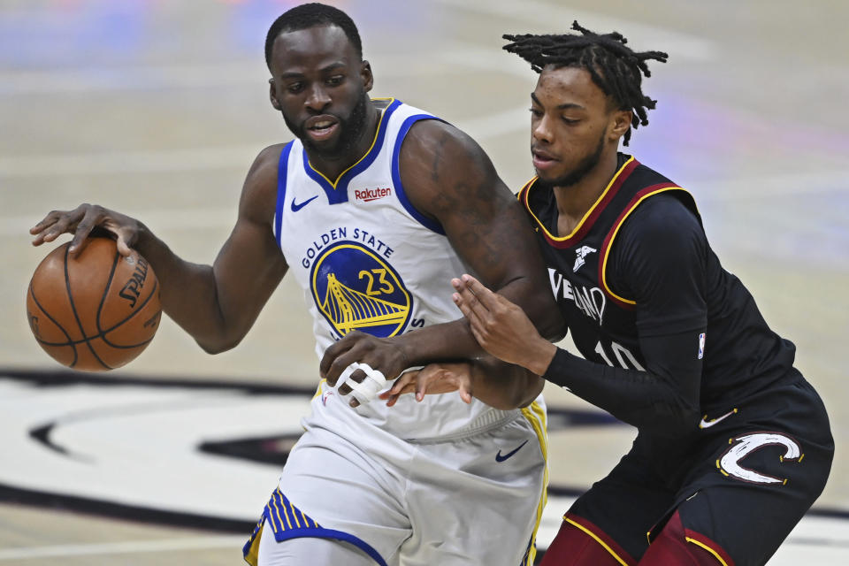 Golden State Warriors' Draymond Green (23) drives on Cleveland Cavaliers' Darius Garland (10) during the second half of an NBA basketball game Thursday, April 15, 2021, in Cleveland. (AP Photo/David Dermer)