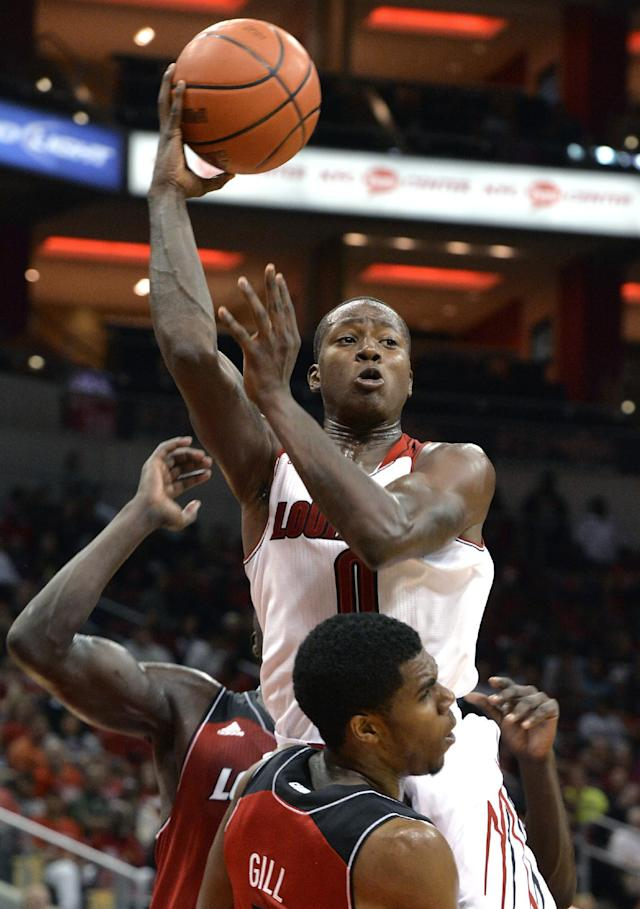Louisville's Terry Rozier, center, throws an outlet pass over the defense of Anton Gill during the NCAA college basketball team's scrimmage Saturday, Oct. 5, 2013, in Louisville, Ky. (AP Photo/Timothy D. Easley)