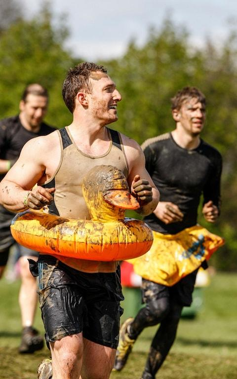 """One Sunday morning, Will Dean informed his girlfriend Katie: """"I am going to electrocute thousands of people."""" Unfazed, she continued reading her newspaper. But the Sheffield-born founder ofToughMudder– the now-globally successful obstacle course series which comes to Gloucestershire's Badminton Estate this weekend – was devilishly serious. """"I started calling engineering companies, saying: 'Hello, we'reToughMudder, we want to shock people with electricity,'"""" explains Dean, 36, who launched his first """"weekend obstacle course for adults"""" in Allentown, Pennsylvania, in May 2010, after studying a MBA at Harvard Business School. """"You'd get a pause and then the line would go dead. People thought they were being pranked."""" In the Tough Mudder innovations lab, human guinea pigs spend their mornings running through hay bales and dipping their extremities in buckets of ice The obstacle called Electroshock Therapy, which involves running through wires fizzing with 10,000 volts (triple the sting of your average electric fence), is now the event's signature challenge. """"As CEO, I have a unique role in all this because I am also the majority shareholder. People said: """"Will, we can't do this."""" I was saying: """"Yes, we can. We can have a board meeting and get it approved in two seconds. Look, it just happened…'"""" Dean spent five years working as a UK counter-terrorism officer in the Middle East and Afghanistan until, stifled by bureaucracy, he sought entrepreneurial fulfilment. His Harvard tutors called his business plan """"optimistic"""". At the inaugural edition, he prayed for 500 customers and got 4,500. There are now 130 annualToughMudderevents in 11 countries with 3 million entrants worldwide so far. This weekend's clientele have paid up to £139 to take on a 10- to 12-mile course littered with tunnels, nets, walls, fire, ice and mud. The company's annual revenues now exceed $100m. Mud Run Electroshock Wire Caught on Neck 00:27 Obstacles are conjured up at an """"Innovation Lab"""" in Pennsylva"""