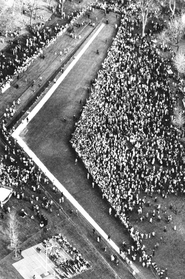 Crowds gather around the new Vietnam Veterans Memorial during the dedication on the National Mall in Washington, D.C. on Saturday, Nov. 15, 1982. The monument is designed by architect Maya Ying Lin. The ceremonies ended on Sunday with a Eucharist service at the National Cathedral. (AP Photo/Charles Pereira)