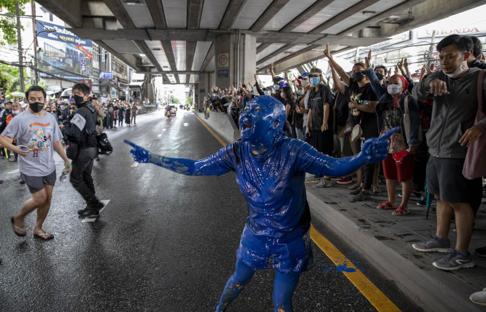 A pro-democracy protester covered in blue paint gestures on a road during a protest in Udom Suk, suburbs of Bangkok, Thailand, Saturday, Oct. 17, 2020. The authorities in Bangkok shut down mass transit systems and set up roadblocks Saturday as Thailand's capital faced a fourth straight day of determined anti-government protests. (AP Photo/Gemunu Amarasinghe)