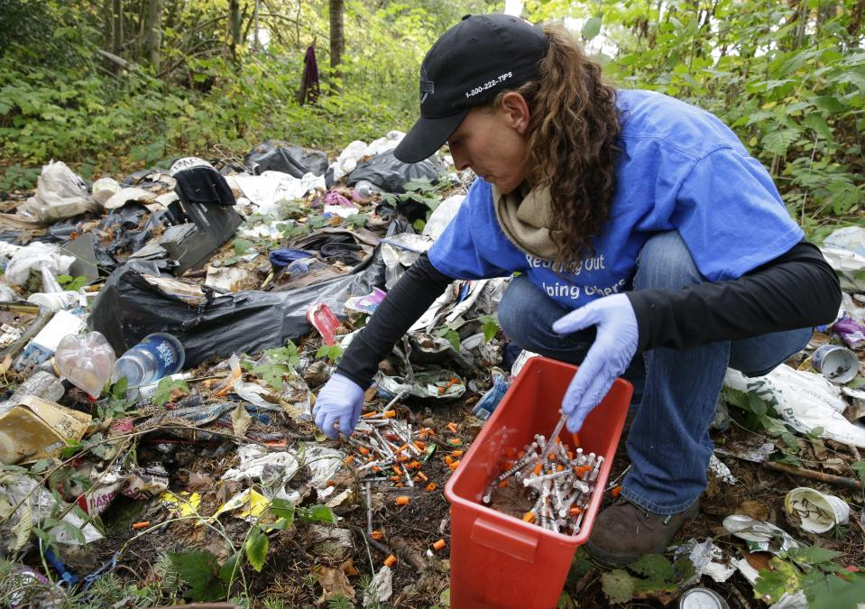 FILE - In this Nov. 8, 2017 file photo, Steph Gaspar, a volunteer outreach worker with The Hand Up Project, an addiction and homeless advocacy group, cleans up needles used for drug injection that were found at a homeless encampment in Everett, Wash. The U.S. Centers of Diseases Control and Prevention says 42,000 people died of overdoses in 2016 from opioids, a class of drug that includes powerful prescription painkillers such as OxyContin and Vicodin; illegal heroin; and fentanyl, a strong synthetic drug sold both through prescriptions and on the street. (AP Photo/Ted S. Warren)
