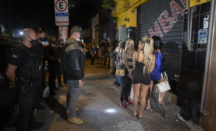 A policeman talks with a woman outside a night club after it was shut down during a police operation against illegal and clandestine gatherings that authorities believe are partly responsible for fuelling the spread of COVID-19, in Sao Paulo, Brazil, early Sunday, April 11, 2021. (AP Photo/Andre Penner)