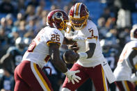 Washington Redskins quarterback Dwayne Haskins (7) hands off to running back Adrian Peterson (26) during the first half of an NFL football game against the Carolina Panthers in Charlotte, N.C., Sunday, Dec. 1, 2019. (AP Photo/Brian Blanco)