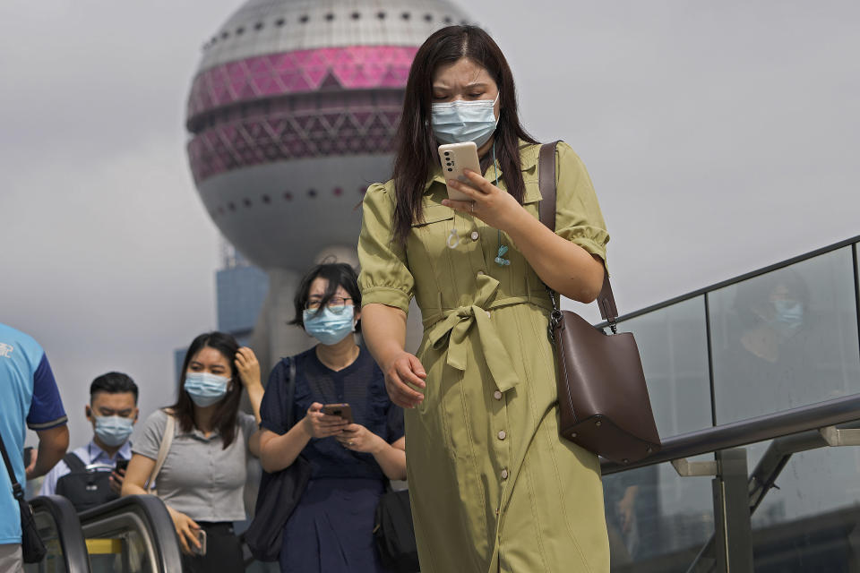 People wearing face masks to help protect from coronavirus using their smartphones walk on a pedestrian overhead bridge in front of the Oriental Pearl TV Tower at the Pudong Financial District in Shanghai, China, on Aug. 25, 2021. Chinese regulators will exercise greater control over the algorithms used by Chinese technology firms to personalize and recommend content, in the latest move in a regulation spree across the internet sector. (AP Photo/Andy Wong)