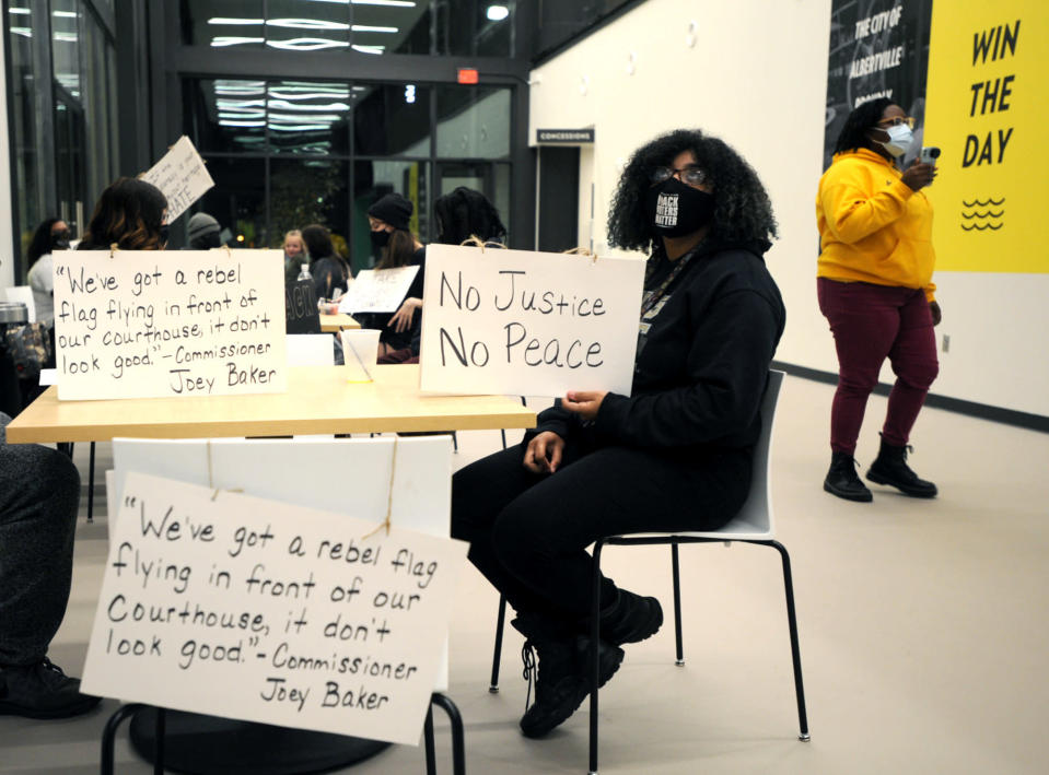 Unique Morgan Dunston, right, participates in a sit-in protest in her hometown of Albertville, Ala., on Wednesday, Dec. 9, 2020. Dunston has been leading regular demonstrations since August against a Confederate monument and flag located on the lawn of the Marshall County Courthouse. (AP Photo/Jay Reeves)