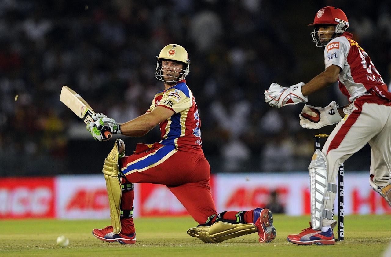 Royal Challengers Bangalore's wicket-keeper Nitin Saini watches as Royal Challengers Bangalore's batsman AB de Villiers (L) plays a shot during the IPL Twenty20 cricket match between Kings XI Punjab and Royal Challengers Bangalore at PCA Stadium in Mohali on April 20, 2012.  AFP PHOTO/ Prakash SINGH RESTRICTED TO EDITORIAL USE. MOBILE USE WITHIN NEWS PACKAGE (Photo credit should read PRAKASH SINGH/AFP/Getty Images)