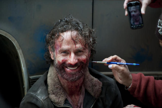 <p>Rick Grimes had just bitten the jugular out of Claimer Joe's neck, but Andy Lincoln is all smiles while getting a touch up on the bloody aftermath of his face.<br><br>(Photo: AMC) </p>
