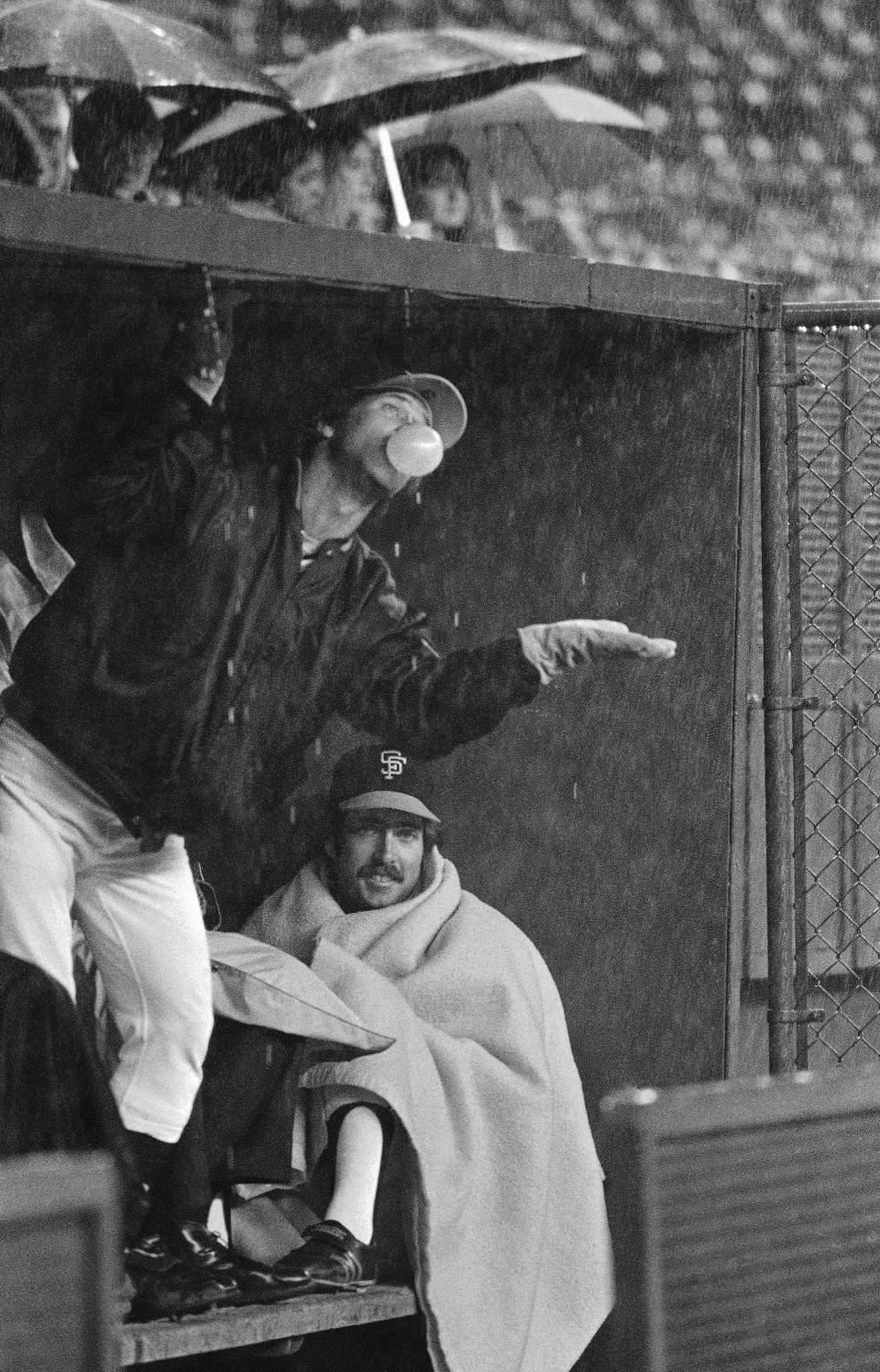 FILE - In this April 1980 file photo, San Francisco Giants catcher Mike Sadek checks the weather as teammate Greg Minton chooses to keep warm under a blanket as the Giants sat out a rain delay before a baseball game with the Cincinnati Reds in Cincinnati. Sadek, a popular backup catcher who played all eight of his major league seasons with the Giants, has died. He was 74. The team announced Sadek died Wednesday, Jan. 20, 2021, in San Andreas, Calif., following a short illness. (AP Photo, File)