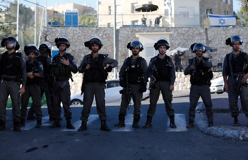 Israeli security forces stand guard as Palestinian residents of the east Jerusalem Palestinian neighbourhood of Jabal Mukaber demonstrate against the remaining checkpoints that were installed the previous month on November 12, 2015