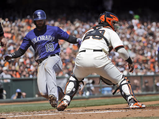 Colorado Rockies' Charlie Blackmon (19) scores past San Francisco Giants catcher Hector Sanchez, right, on a sacrifice fly hit by Troy Tulowitzki during the third inning of a baseball game on Saturday, April 12, 2014, in San Francisco. (AP Photo/Marcio Jose Sanchez)