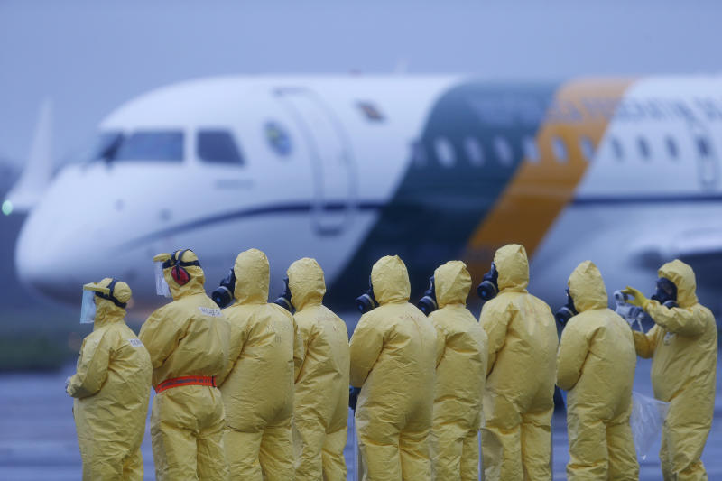 Soldiers stand on the tarmac wearing protective suits, as they watch the arrival of Brazilians repatriated from Wuhan, China, the epicenter of a new virus, at the air force base in Anapolis, Brazil, Sunday, Feb. 9, 2020. Dozens of Brazilians landed early Sunday morning at the airbase in the Brazilian state of Goias, where they will spend the next 18 days in quarantine. (AP Photo/Beto Barata)
