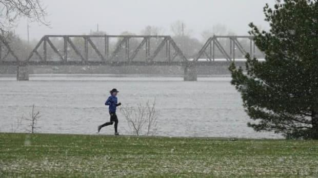 A runner braves the late snowfall along the Ottawa River on Wednesday. Gyms are closed during Ontario's stay-at-home order, but distanced exercise is still considered an essential reason for an outing. (Francis Ferland/CBC - image credit)