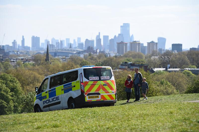Police pass a family out walking on Primrose Hill, London, as the UK continues in lockdown to help curb the spread of the coronavirus.