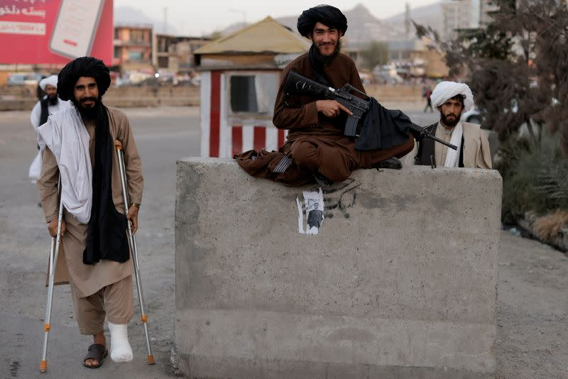 FILE PHOTO: Taliban fighter Mira Jan Himmat, 30, and Rafiullah, 26, from Helmand province smile as they stand guard in a checkpoint in Kabul