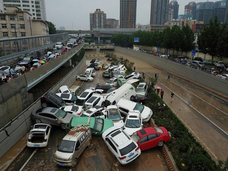 Piles of cars swept away by floods lie at the entrance to a tunnel in Zhengzhou