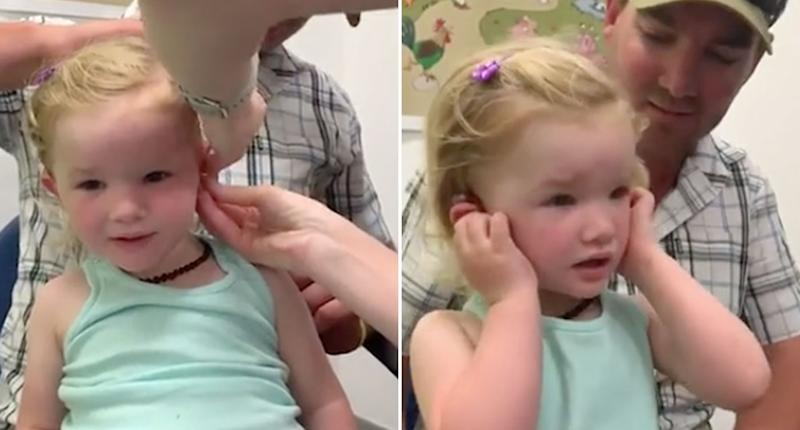 Macy Storer receives her hearing aid and hears sound fo the first time while sitting on her dad Tristan's lap.