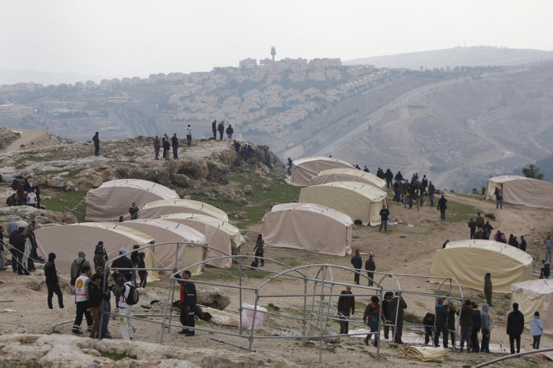 Palestinians, together with Israeli and foreign activists, stand near newly-erected tents in the 'outpost ' of Bab al-Shams (Gate of the Sun) an area known as E1 near Jerusalem, Friday, Jan 11, 2013. In the background the Israeli settlement of Ma'aleh Adumim is seen. Palestinian activists pitched tents in the West Bank on Friday to protest Israeli plans to build a large Jewish settlement on a key route through the territory. The E-1 settlement would block east Jerusalem from its West Bank hinterland — both territories captured by Israel during the 1967 Mideast war. (AP Photo/Majdi Mohammed)