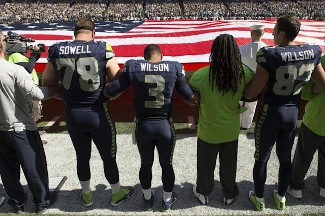 <p>Seattle Seahawks offensive tackle Bradley Sowell (78), left, quarterback Russell Wilson (3) and tight end Luke Willson (82) join arms during the National Anthem before the start of a game against the Miami Dolphins at CenturyLink Field. Mandatory Credit: Troy Wayrynen-USA TODAY Sports </p>