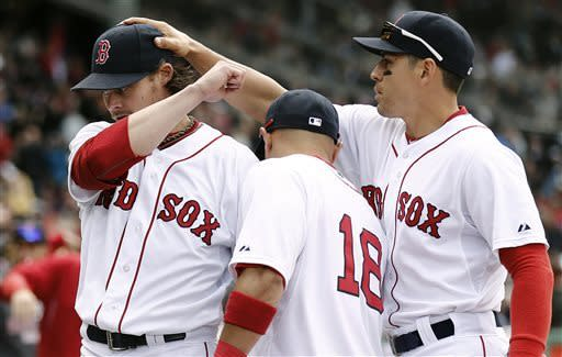 Boston Red Sox starting pitcher Clay Buchholz, left, is congratulated by Jacoby Ellsbury and Shane Victorino (18) while leaving the field after losing his no-hitter in the eighth inning of a baseball game against the Tampa Bay Rays at Fenway Park in Boston, Sunday, April 14, 2013. (AP Photo/Winslow Townson)