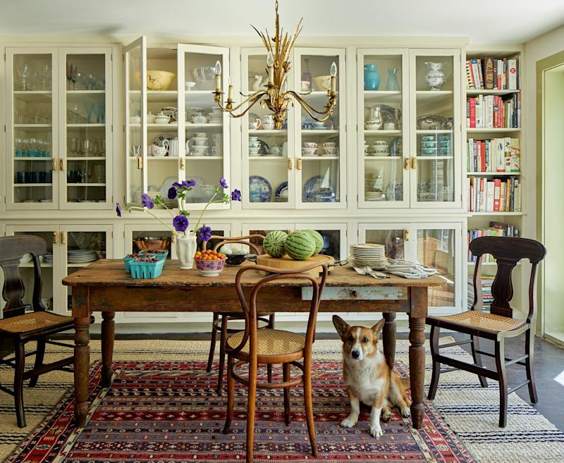 In the kitchen, cabinets by Over Mountain Builders hold ten Have's extensive collection of china. Antique dining table; Turkish rug atop Bunny Williams rug.