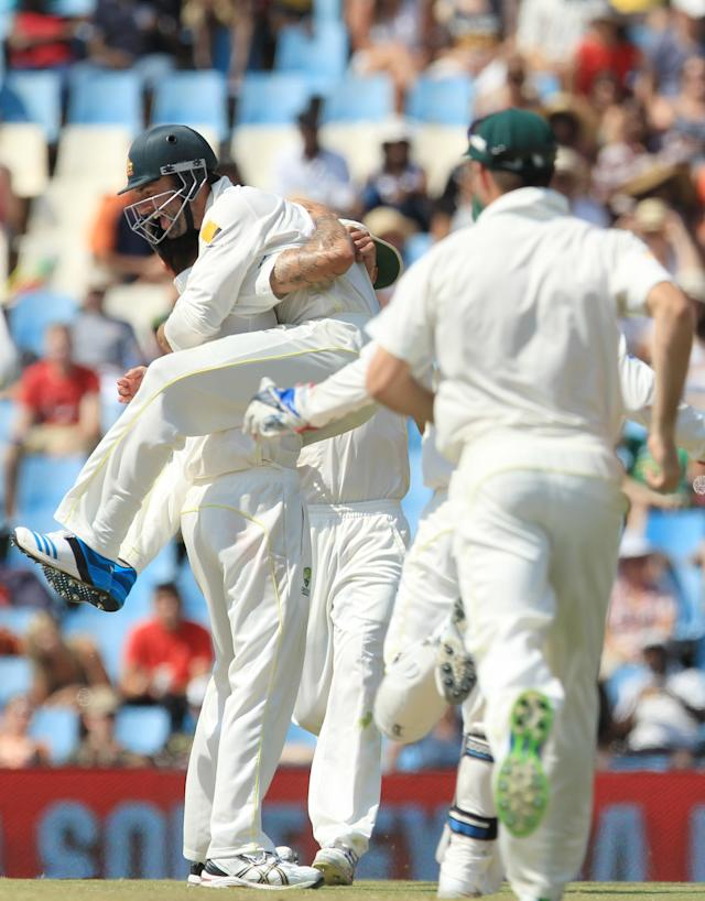 Australia's fielder Alex Doolan, center, jumps onto bowler Mitchell Johnson, left, after taking a catch on the fourth day of their cricket test match against South Africa at Centurion Park in Pretoria, South Africa, Saturday, Feb. 15, 2014. (AP Photo/ Themba Hadebe)