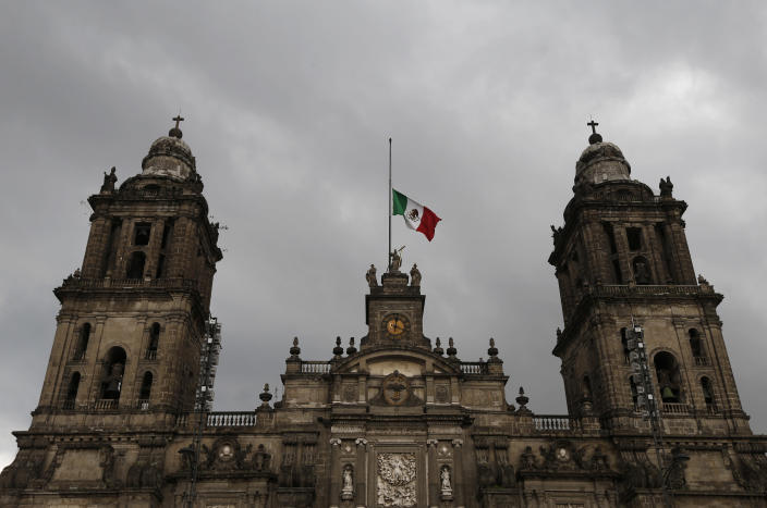 FILE - In this Sept. 9, 2017 file photo, a Mexican flag flies at half-mast on the Metropolitan Cathedral during three days of mourning following a deadly earthquake and hurricane, in Mexico City. The Vatican's announcement that it is sending an investigative commission to Mexico in March 2020 to look into cases of clergy abuse could become a turning point in a country that's home to the second largest number of Catholics in the world. (AP Photo/Marco Ugarte, File)