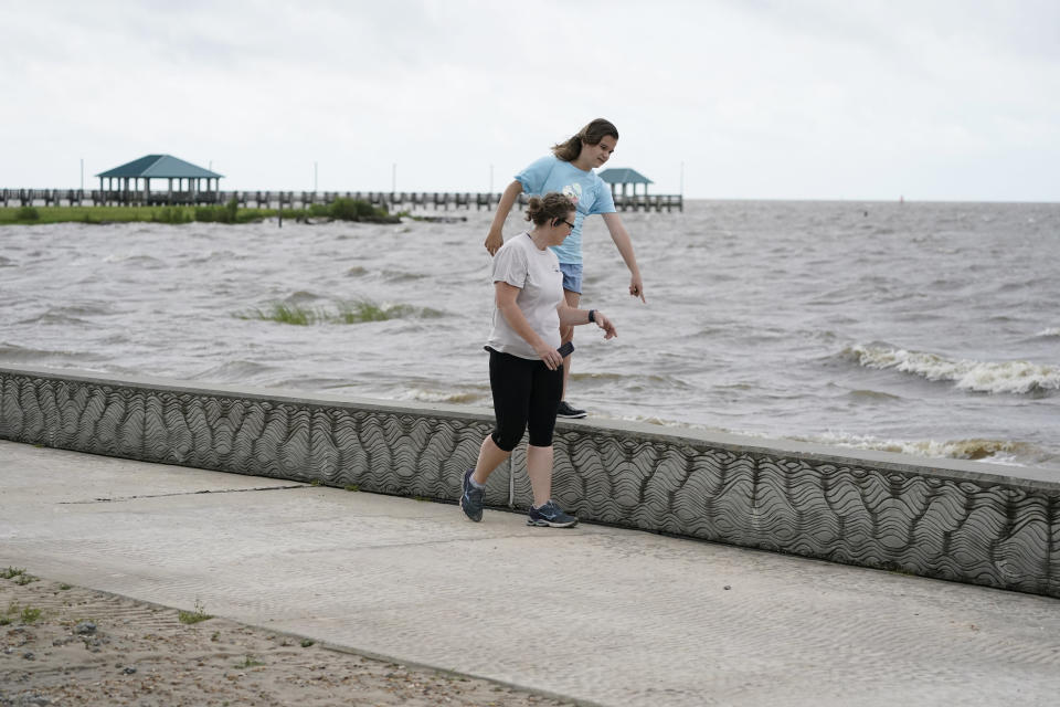 Lucy Trott, 11, points out some sand crabs to her mother Katherine Lott, as they walk along the walkway on Front Beach Drive in Ocean Springs, Miss., Saturday, June 19, 2021. The mother and daughter spoke of enjoying the stiff breeze and brisk wave action from the remnants of Tropical Storm Claudette. (AP Photo/Rogelio V. Solis)