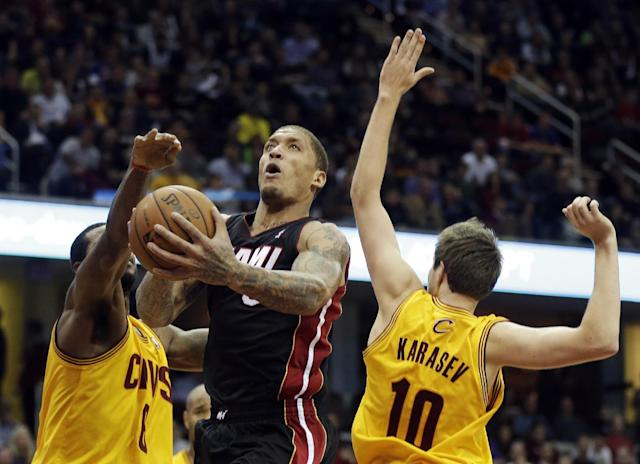 Miami Heat's Michael Beasley shoots between Cleveland Cavaliers' Earl Clark and Sergey Karasev (10) in the fourth quarter of an NBA basketball game Wednesday, Nov. 27, 2013, in Cleveland. The Heat won 95-84. (AP Photo/Mark Duncan)
