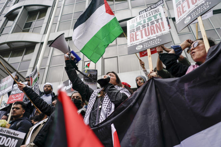 People hold placards and Palestinian flags as they march in solidarity with the Palestinian people amid the ongoing conflict with Israel, during a demonstration in London, Saturday, May 15, 2021. (AP Photo/Alberto Pezzali)