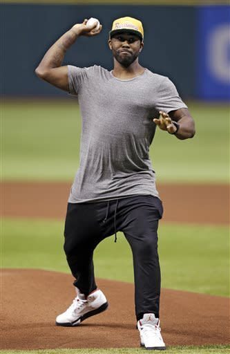 New Tampa Bay Buccaneers cornerback Darrelle Revis throws out the ceremonial first pitch before a baseball game between the Tampa Bay Rays and the New York Yankees, Monday, April 22, 2013, in St. Petersburg, Fla. The three-time All-Pro acquired from the New York Jets was formally introduced Monday as the newest member of a Buccaneers defense that ranked last in the NFL in pass defense in 2012. (AP Photo/Chris O'Meara)