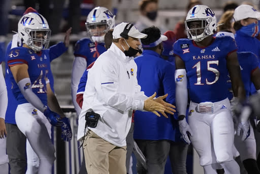 Kansas coach Les Miles stands near players during the first half of the team's NCAA college football game against TCU in Lawrence, Kan., Saturday, Nov. 28, 2020. (AP Photo/Orlin Wagner)