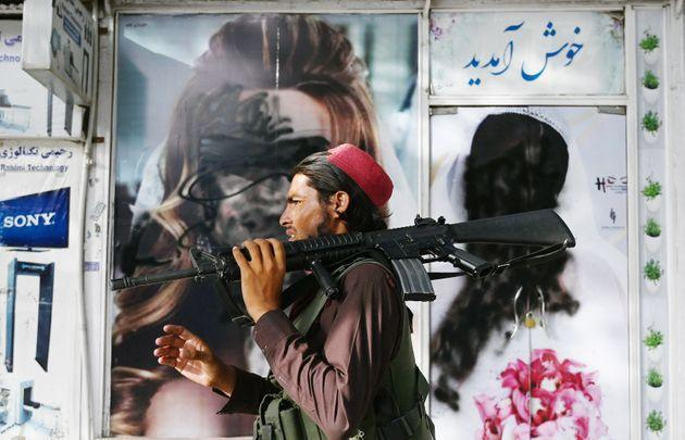 A Taliban fighter walks past a beauty saloon with images of women defaced using a spray paint in Shar-e-Naw in Kabul on August 18, 2021. (Photo by Wakil KOHSAR / AFP) (Photo by WAKIL KOHSAR/AFP via Getty Images) (Photo: WAKIL KOHSAR via Getty Images)